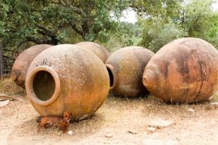 Eros junto a un tesoro de vasijas antiguas.