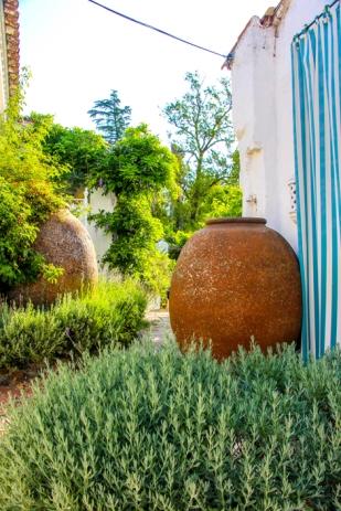 """Hierbas aromáticas, vasijas y telas de rayas visten los caminos del """"cottage""""."""
