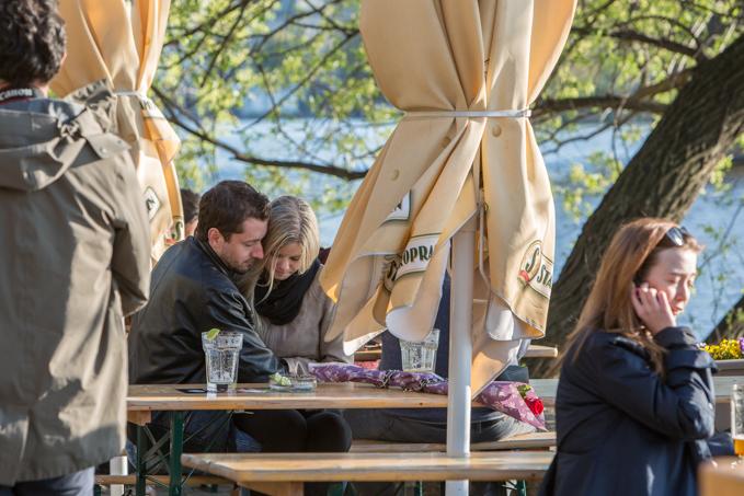 Atardecer, música y cerveza en mesas compartidas.