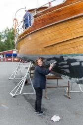 Pintando el casco de su barco de madera, la señora lleva décadas navegando por el fiordo.